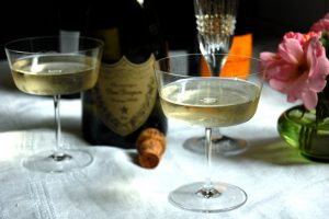 coupes of champagne in glasses with Dom Perignon and Veuve sparkling wine bottles