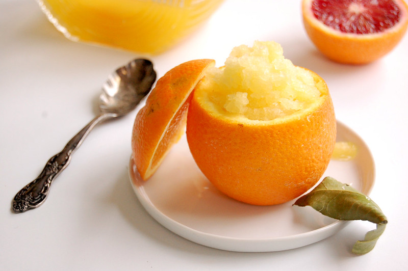 homemade orange granita in orange shell with juice and spoon