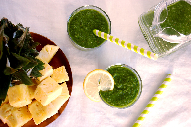 glasses of best pineapple kale green smoothie on tablecloth with straw