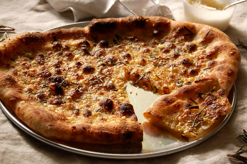 parmesan rosemary pizzetta on pizza tray with cheese