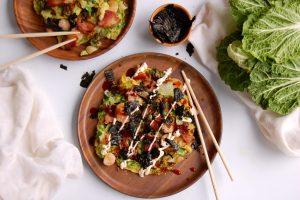okonomiyake japanese cabbage pancake on wooden dish with chopsticks sauce and nori