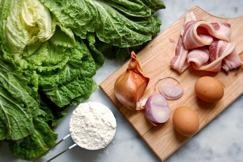 okonomiyaki ingredients cabbage flour bonito shallot bacon on countertop