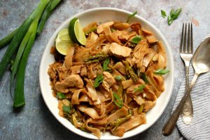 bowl of pad see ew with chicken and lime