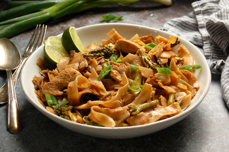 bowl of finished Thai rice noodles stir-fried with chicken broccoli and lime