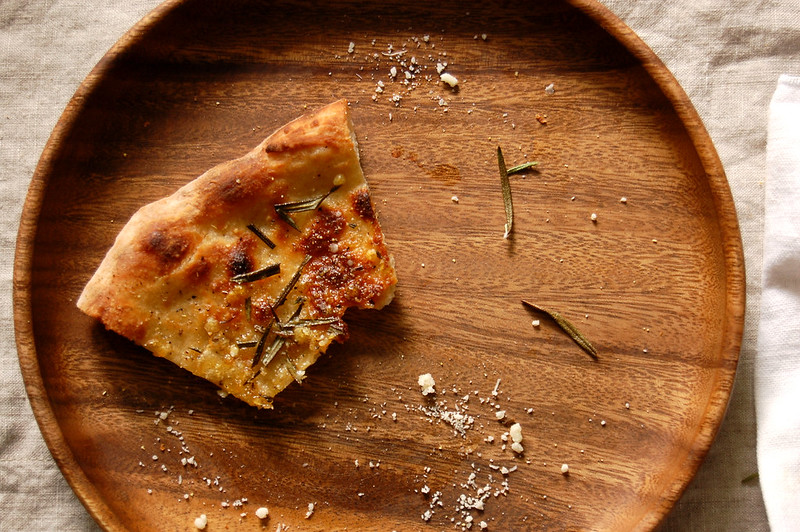 piece of pizzetta on wooden plate mostly eaten