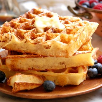 stack of waffles with blueberries and syrup
