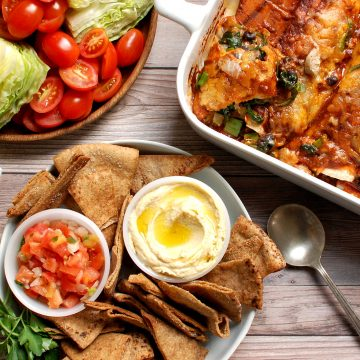 spread of football food for super bowl 2021 chips dip enchiladas salad