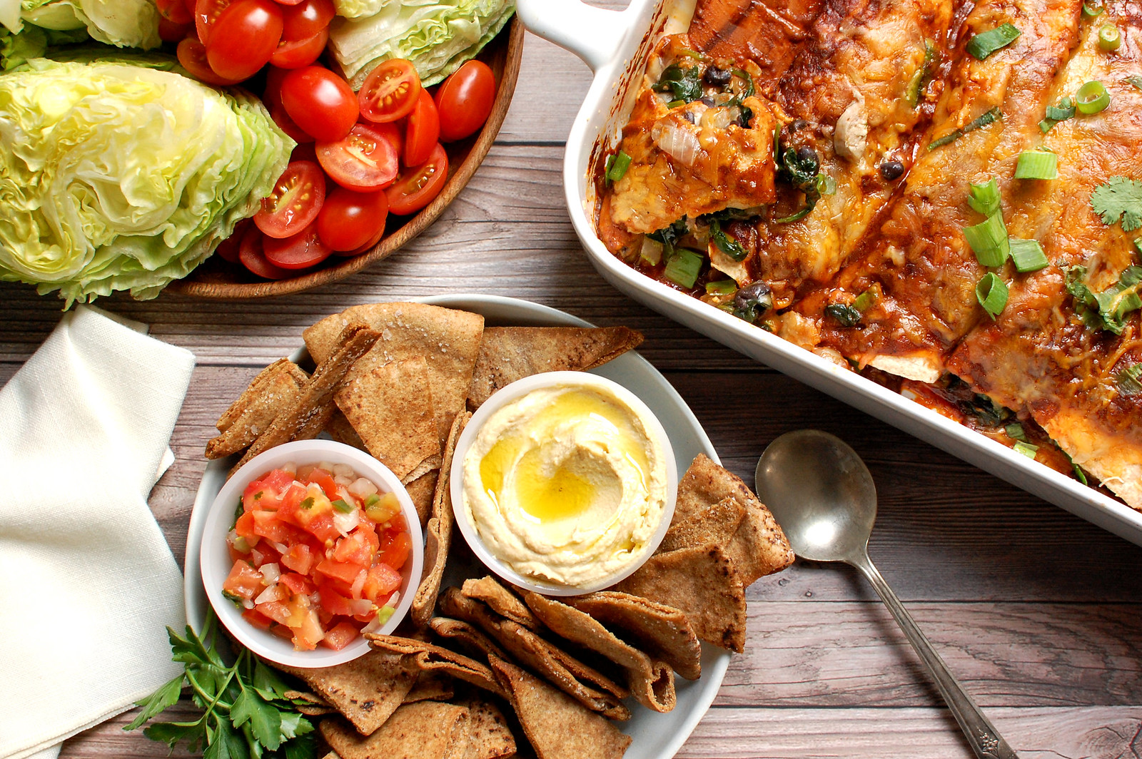 spread of football food for super bowl 2021 chips dip enchiladas salad