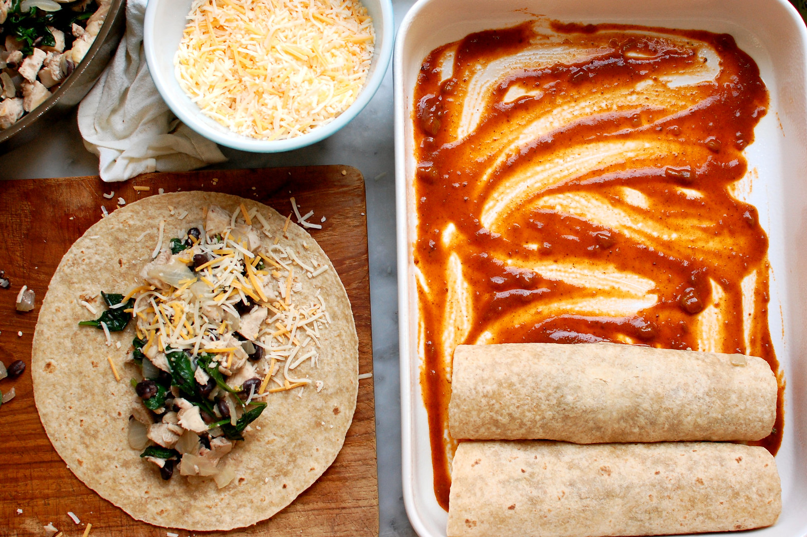 enchilada ingredients being rolled in tortillas with cheese and enchilada sauce