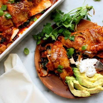 wooden plate of chicken and black bean enchiladas with avocado and cilantro