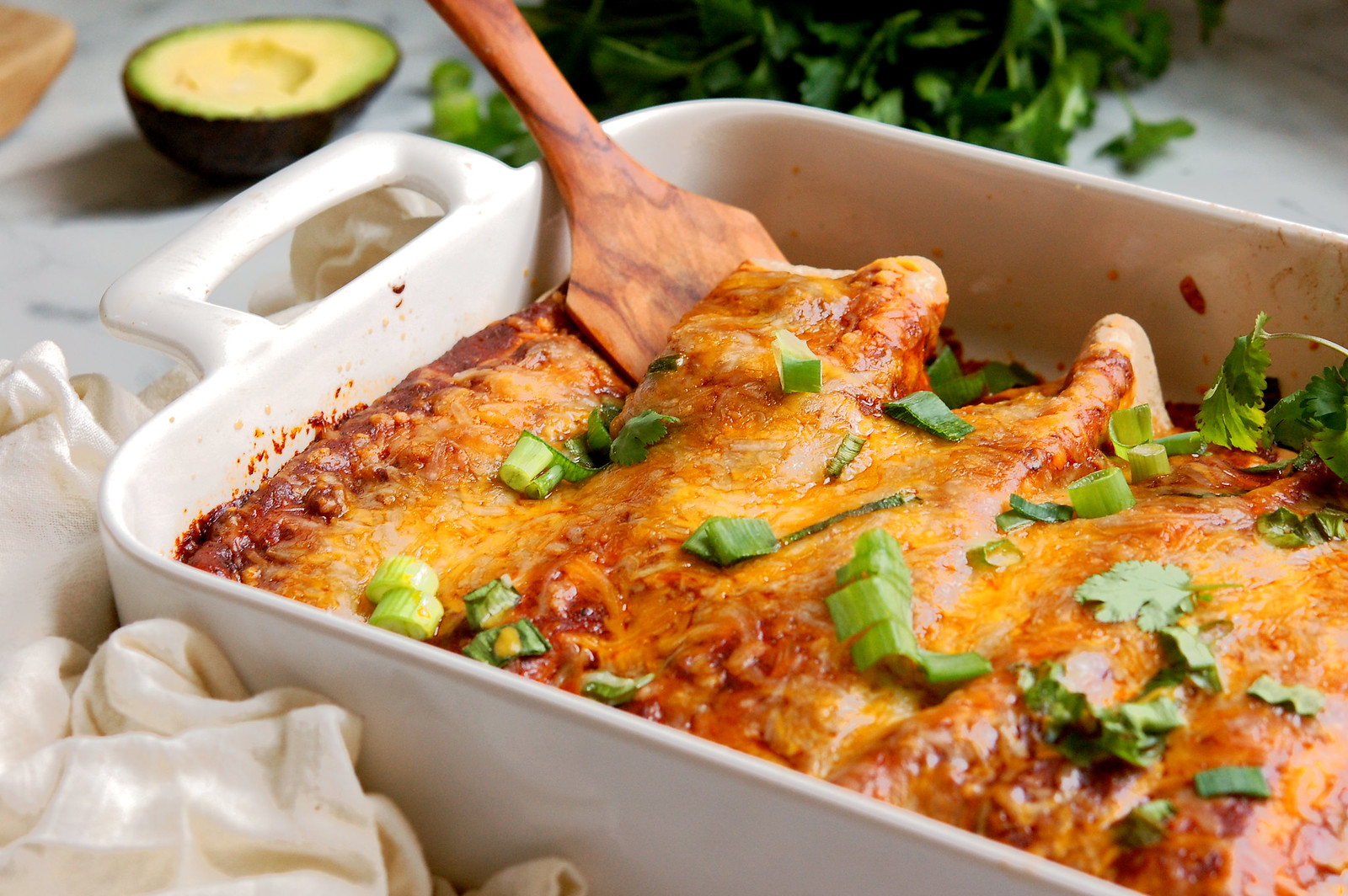 chicken black bean enchiladas baked in casserole with melted cheese and scallions