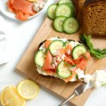 cured salmon cucumber smorrebrod toast on wooden board with garnishes