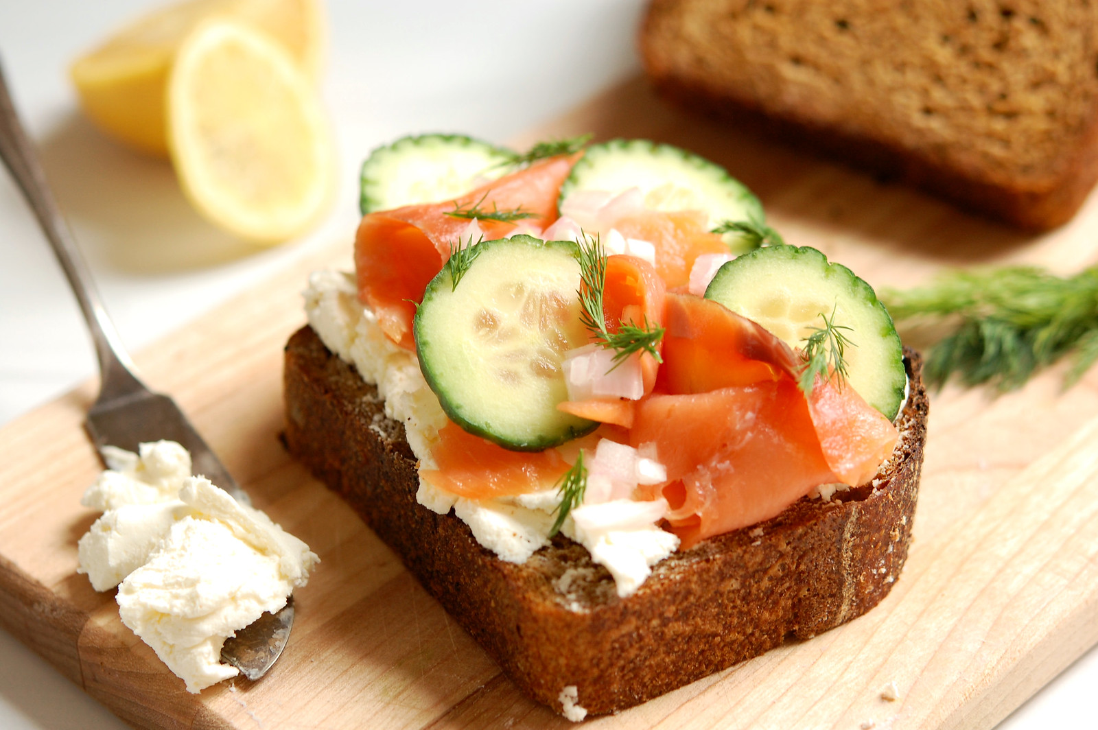 cured cured salmon cucumber smorrebrod toast on wooden board with garnishes cucumber smorrebrod toast on wooden board with garmishes