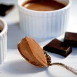 spoonful of silky dark chocolate pudding with ramekins
