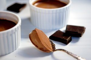 spoonful of silky dark chocolate pudding with ramekins
