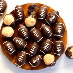 game day dessert chocolate peanut butter buckeye with football design on wood plate