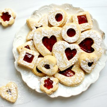 valentine's day linzer sugar cookies with jam on dessert plate