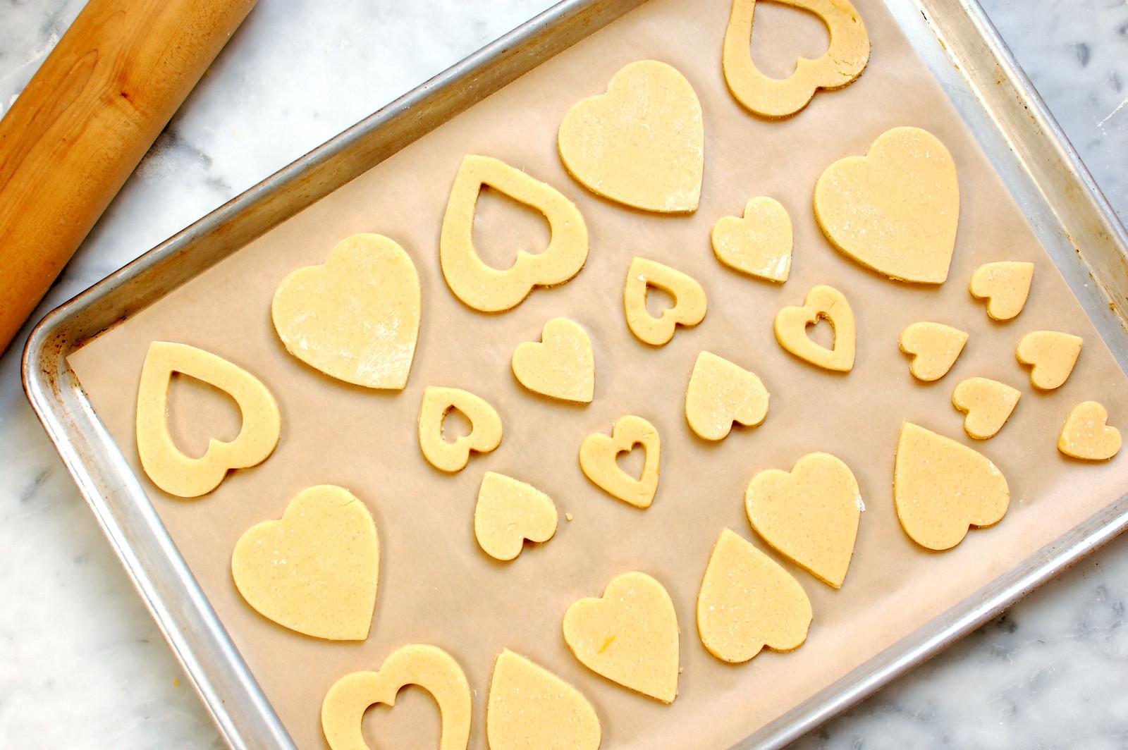 sugar cookie linzer dough heart cutouts on sheet pan ready to bake