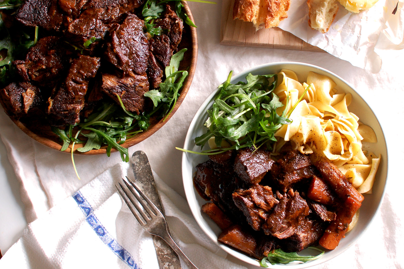 dish of tender red wine braised beef short ribs with noodles and salad