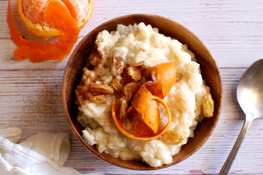 bowl of creamy arborio rice pudding with orange zest and raisins