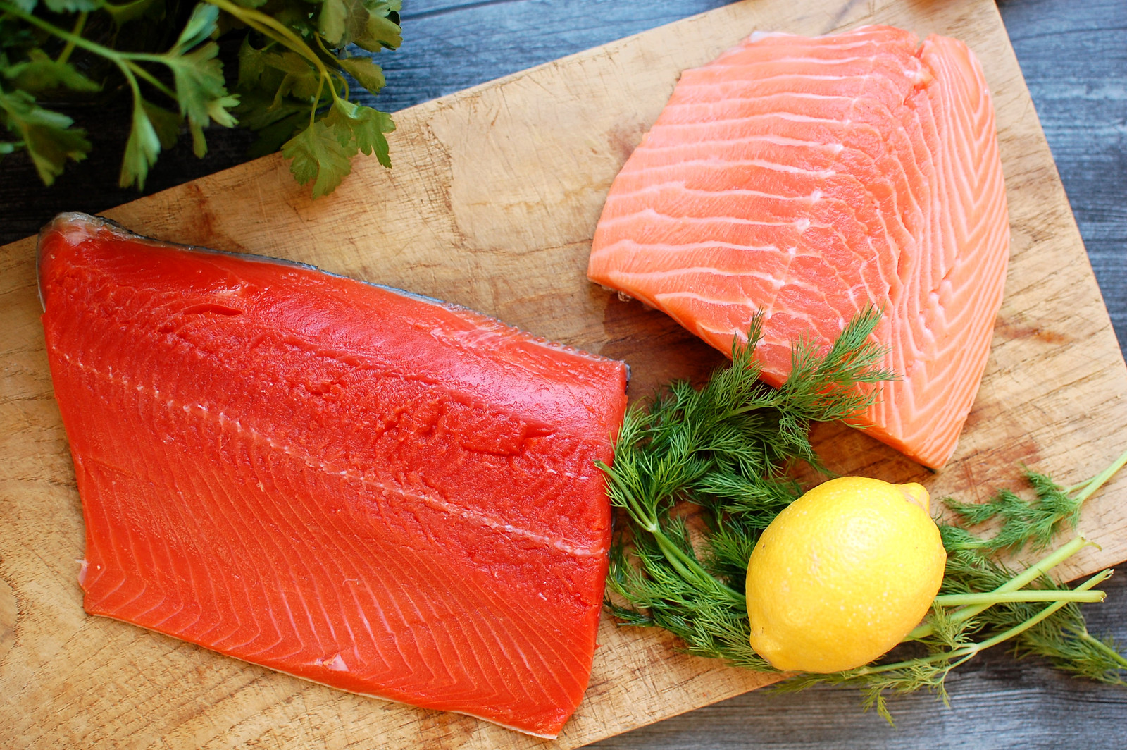 wild and farmed salmon on cutting board with lemon and fresh herbs