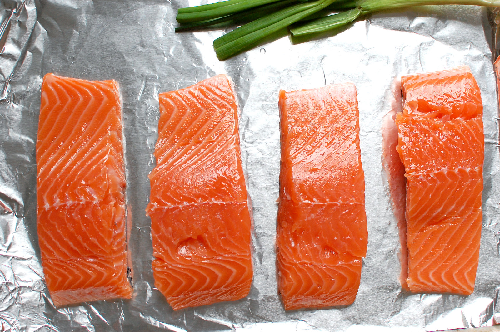 salmon fillets on sheet pan with scallions