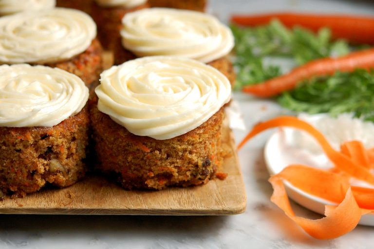 carrot cake and cupcakes on table with carrot peels