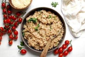 bowl of creamy parmesan whole-grain farro with tomatoes and parsley