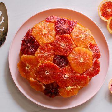 finished poached orange cake on table with cake server