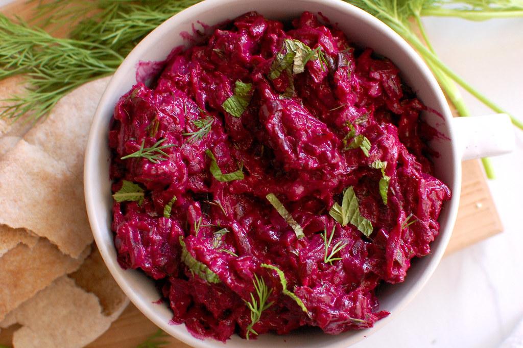 bowl of Israeli Zahav beet tehina and herb salad spread