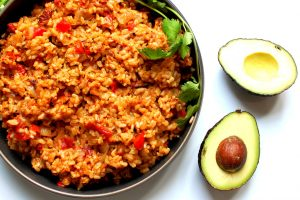 platter of finished mexican or spanish rice with avocado and cilantro