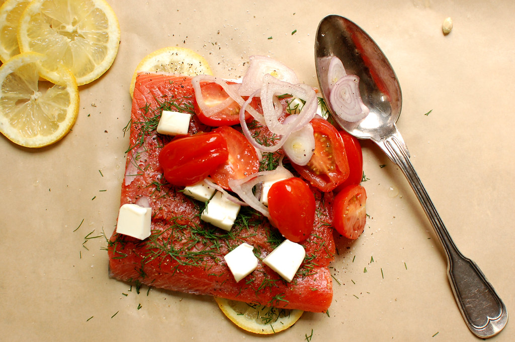 baked salmon and ingredients on parchment before baking dinner en papillote