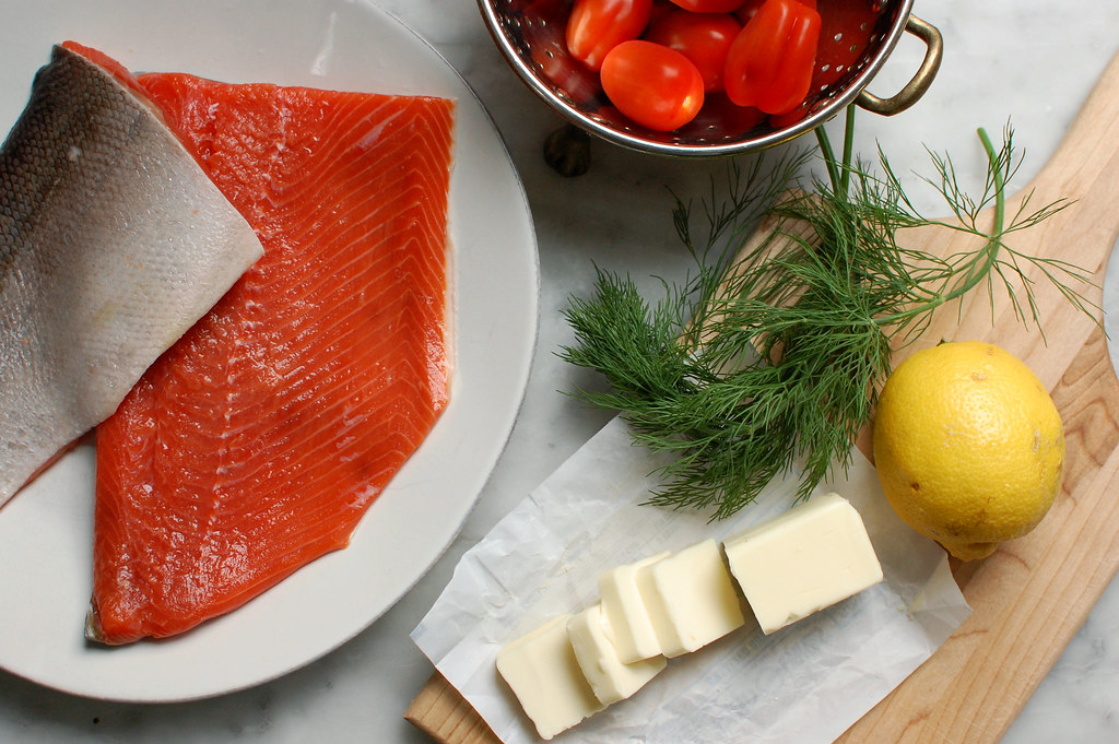 salmon butter dill lemon and tomatoes on kitchen counter