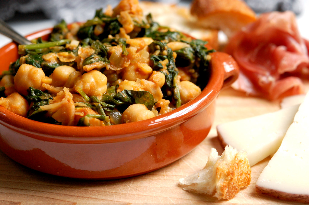 spinach and chickpea Spanish tapas in bowl with bread and cheese