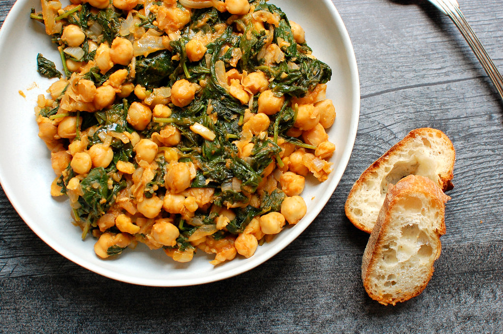bowl of cooked chickpeas and kale Spanish tapas with bread