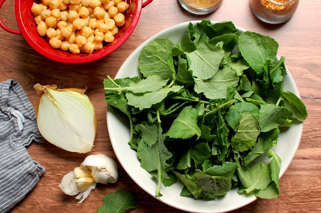 kale spinach chickpeas onion garlic on wooden table