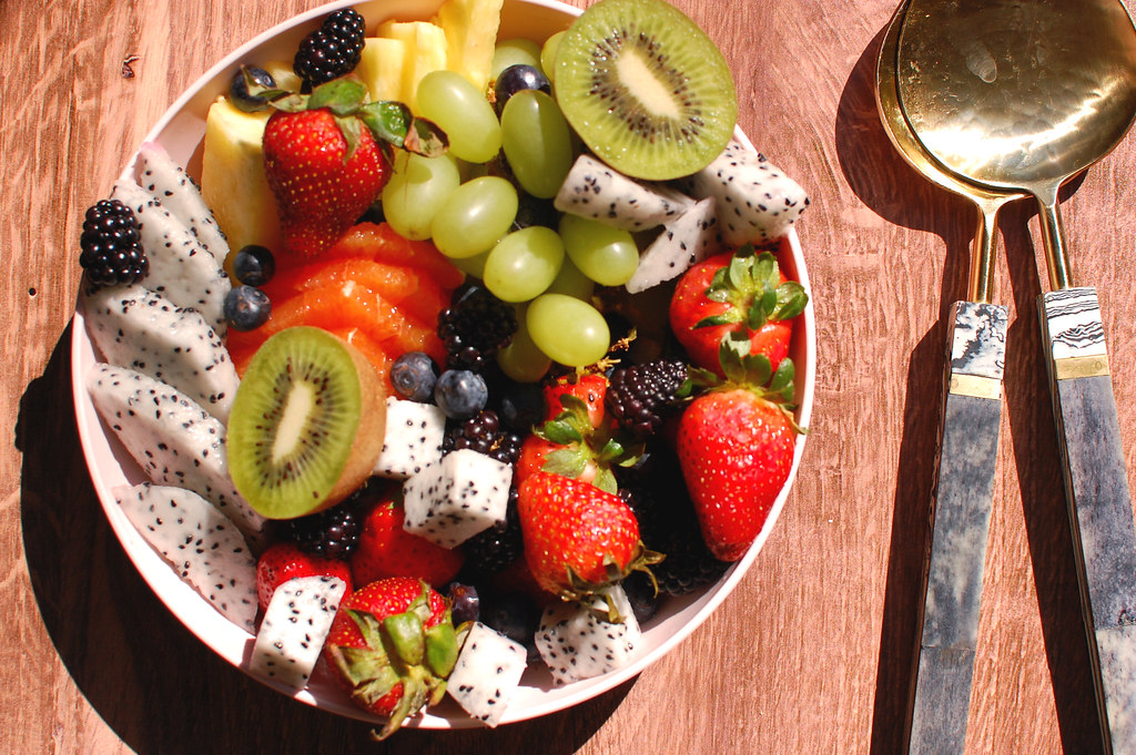 cut tropical fruit salad with serving utensils on wood