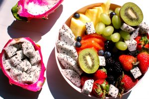 cut dragon fruit in cut fruit salad bowl with ripe dragon fruit on the side