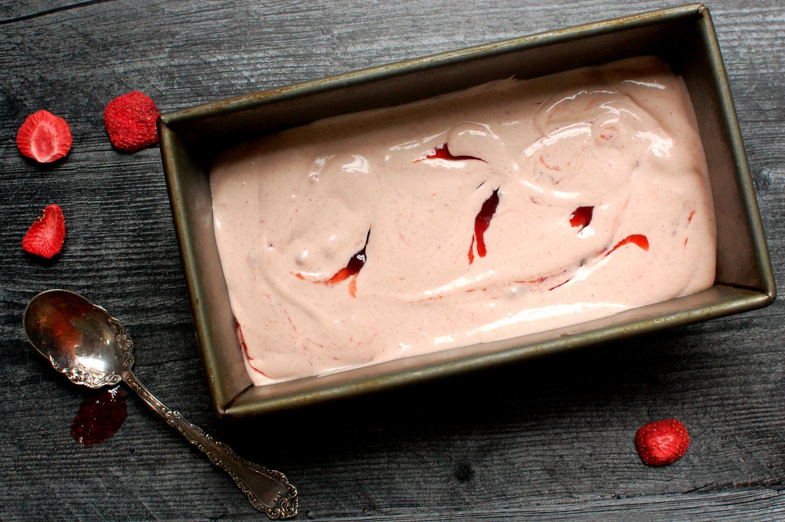 no churn strawberry ice cream in container with scoop strawberry ice cream in bowl with strawberries