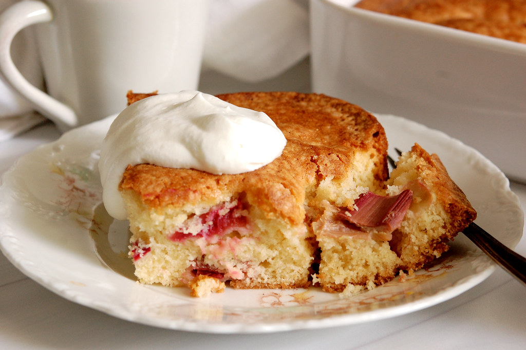 slice of fresh rhubarb cake on plate with whipped cream