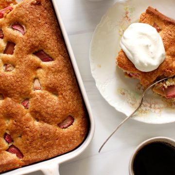 rhubarb cake in cake pan with slice and whipped cream