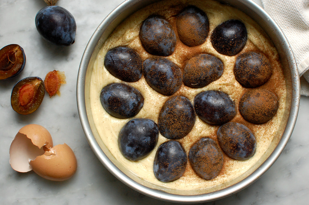 unbaked plum cake in cake pan with plums and cinnamon
