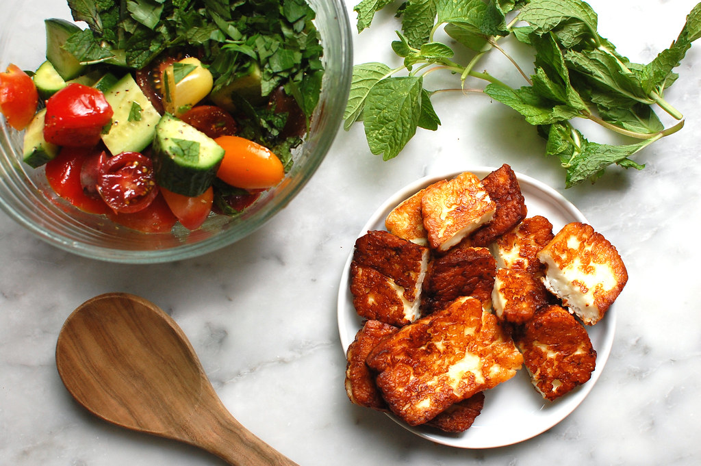 fried halloumi cheese on plate with herby tomato cucumber salad